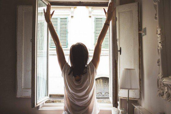 Frau steht auf und streckt sich am Fenster