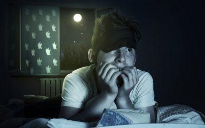 Junge liegt ängstlich im Bett wären hinter ihm der Mond durch das Fenster scheint