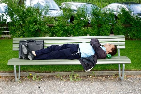 Businessman macht einen Mittagsschlaf auf einer Parkbank