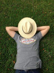 Mann schläft auf einer Wiese mit einem Hut auf dem Gesicht