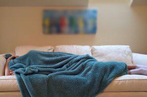 Eine Person schläft auf einem Sofa unter einer Decke