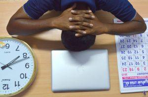 Mann schläft mit dem Kopf auf dem Schreibtisch