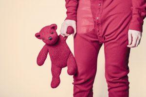 Kind mit einem roten Schlafanzug und einen roten Teddy in der Hand