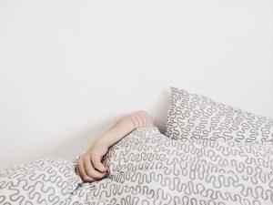 Eine Person schläft unter einer Bettdecke und nur der Arm scheint hervor
