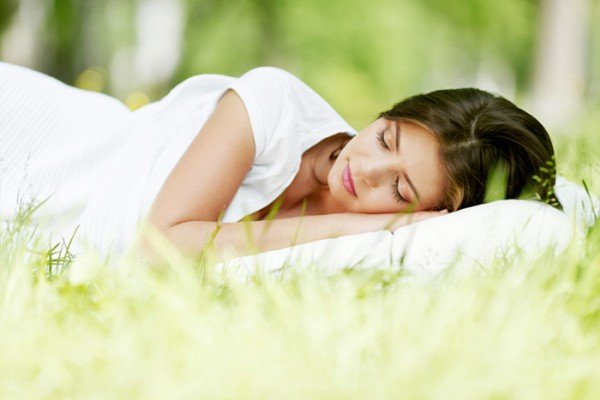 Frau schläft auf der Wiese