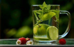 Ein Glas Wasser mit Minze und Limettenscheiben