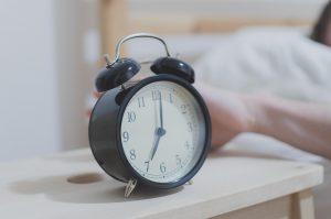 Ein Wecker steht auf einem weißen Nachttisch und wird gerade von einer Hand ausgemacht