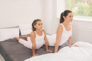 Gymnastik im Bett mit Mutter und Kind