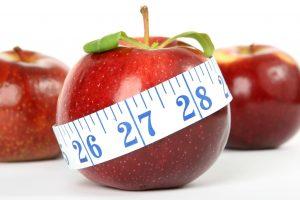 Ein roter Apfel mit einem Maßband umwickelt
