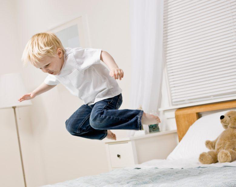 Kleiner Junge springt auf einem Lattenrost und einer Matratze